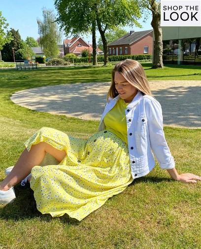 Strallend zwanger in zonnig geel